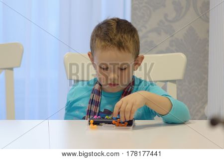 boy playing sitting at a table with a puzzle