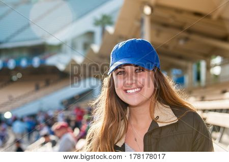 Happy female fan wearing blue cap in outfield bleachers.
