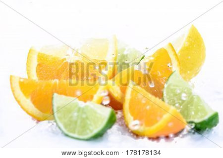 Various types of citrus fruit in splash of water drops