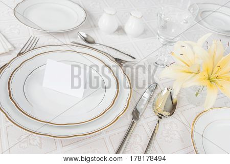 Beautifully decorated table with white plates crystal glasses cutlery and flowers on luxurious tablecloths with guest card
