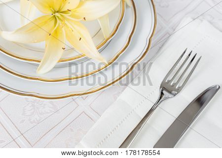 Beautifully decorated table with white plates linen napkin cutlery and flowers on luxurious tablecloths