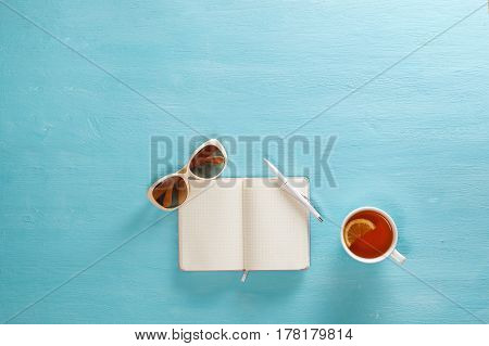 Opened notebook with pen, cup of tea and sunglasses on blue wooden table. Top view. Writing, blogging concept. Copy space.