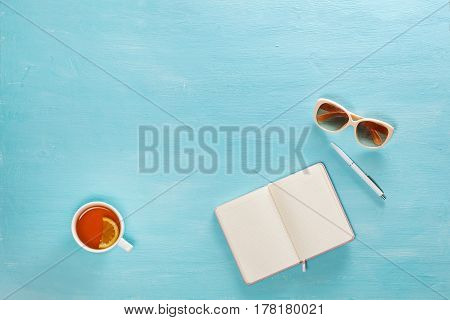 Opened notebook with pen, cup of tea and sunglasses on blue wooden table. Top view. Writing, blogging concept.