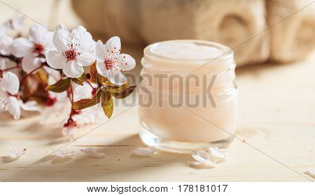 Moisturizing Cream And Cherry Blooms On Wooden Background