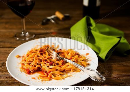 Half-eaten tagliatelle pasta with bolognese ragu and red wine over a rustic table