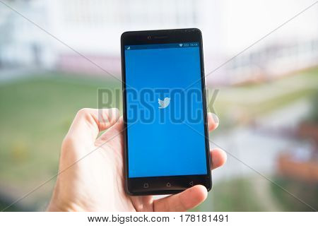 Nitra, Slovakia - March 24 2017: Man hand holding smart phone with social networking service Twitter on the screen. Twitter is an online social networking and microblogging service that enables users to send and read tweets.