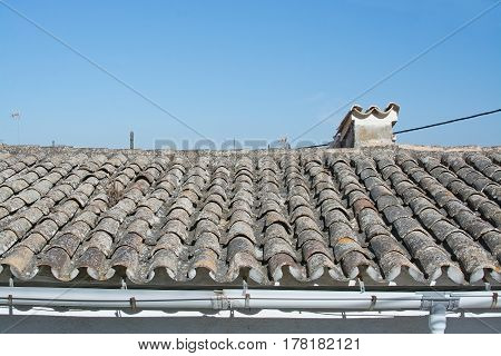 Grungy tiled roof and chimney detail with character and charm against blue sky in Palma Mallorca Spain.