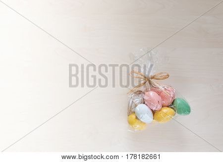Colorful Easter eggs in present on wooden background.