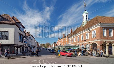 Farnham, UK. 25th March 2017. Pedestrians are walking along The Borough in Farnham at the junction of Castle Street on a sunny spring day.