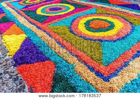 Antigua, Guatemala - March 25 2016: Closeup of handmade dyed sawdust carpet for Good Friday procession in colonial town with most famous Holy Week celebrations in Latin America.