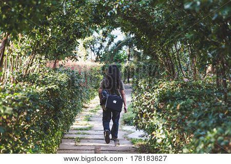 A person walks down a path towards a beautiful courtyard at a resort at Lake Atitlan Guatemala Central America.