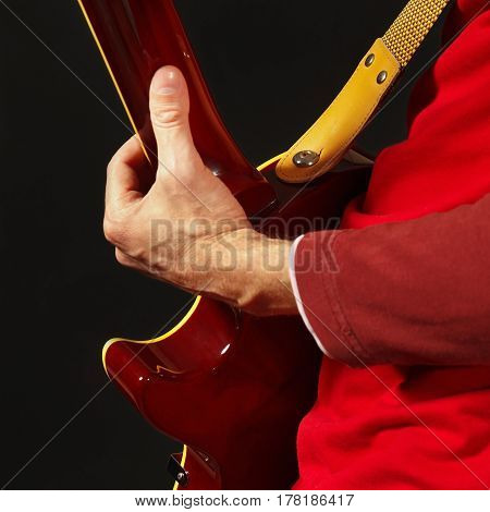 Guitarist playing the guitar on a dark background