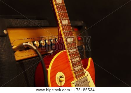 Electric guitar with combo amplifier on the black background. Shallow depth of field low key close up.