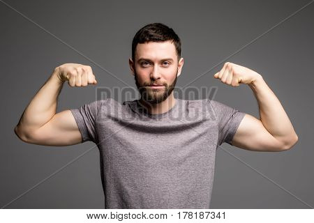Portrait Of A Man In Shirt Showing His Muscles Over Gray Background