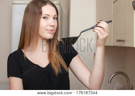 Housewife throwing out garbage in the kitchen opening a cupboard door.