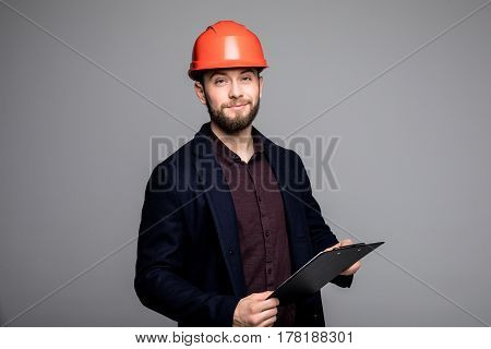 Adult Caucasian Man In A Black Suit And Construction Helmet Holding Black Folder