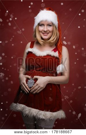 Portrait of a pregnant woman in santa dress