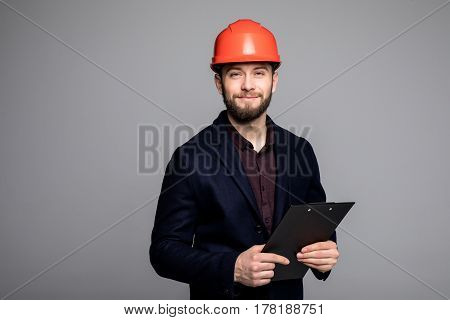 Man In A Black Suit And Construction Helmet Looking To The Side And Holding Black Folder