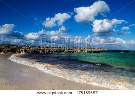 A beautiful tropical cove with rocks, clouds, and waves. New Providence Island, Nassau, Bahamas.