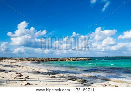 A bright exotic cove with rocks, clouds, and small waves. New Providence Island, Nassau, Bahamas.