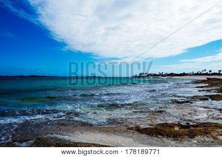 A bright tropical cove with rocks, clouds, and algae. New Providence Island, Nassau, Bahamas.