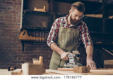 Photo Of Young Handsome Serious Handicraftsman With Safety Glasses Using Grinder And Sandpaper In Ca