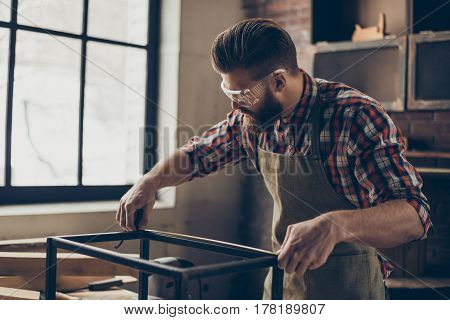 Young Busy Concentrated Carpenter In Checkered Shirt With Safety Glasses Holding A Tape And Measurin