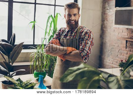 Portrait Of Young Smiling Gardener With Crossed Hands At The Greenhouse Looking After The Flowers An