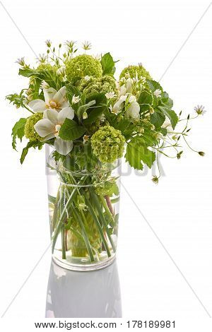 Bouquet of spring flowers in water-glass isolated on white background