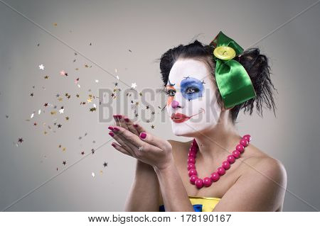 portrait of a clown-girl blowing the tinsel - star.