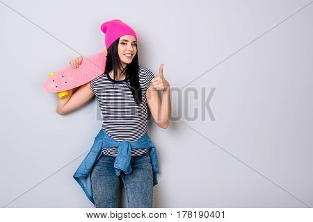Young Girl In Pink Hat And Skateboard On Her Shoulder Smiling And Showing Thumb Up
