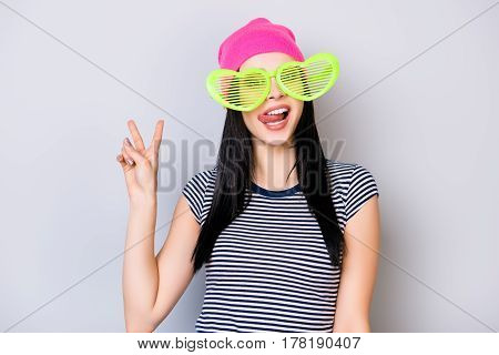 Portrait Of Young Cute Girl In Pink Hat And Big Funny Green Glasses Showing Tongue And V-sign