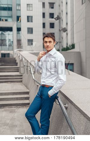 Confident young businessman in white shirt and looking away while standing outdoors with cityscape in the background