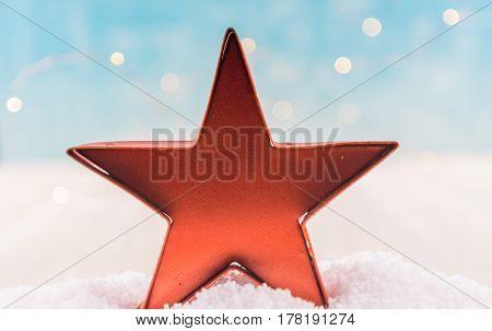 Orange Tin Star Ornament In Snow