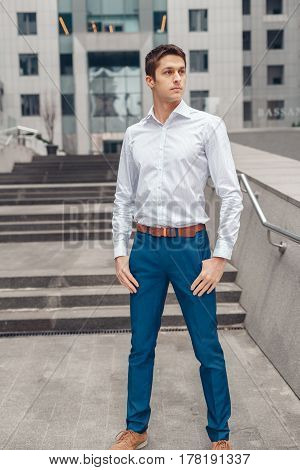 Young handsome businessman standing outside the office on the stairs. Young man in white shirt near the business center.