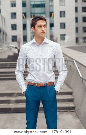 Businessman posing confident and positive in professional workplace office with space.
