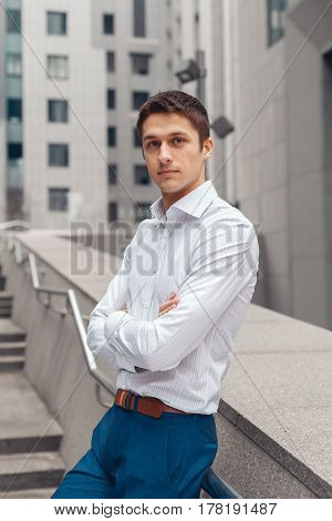 Young business man looking at camera and posing on stairs of office building.