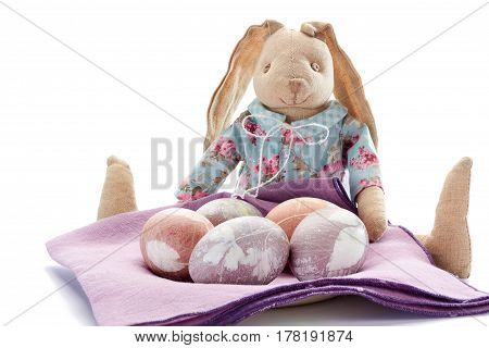 Sitting easter bunny and painted eggs over violet napkin on white background