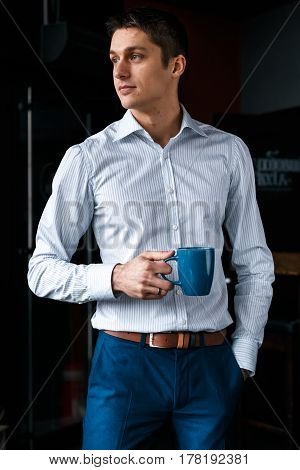 Handsome businessman with the cup in his hands. Coffee break. A young man is standing and drinking coffee.