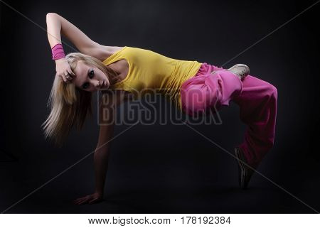 Full-length portrait of a girl dancing on a dark studio background