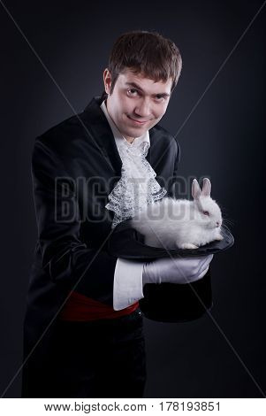 man dressed as a magician pulling a rabbit from his hat