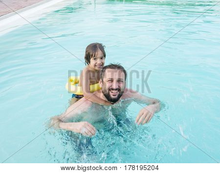 Child splashing in swimming pool having fun leisure activity with father