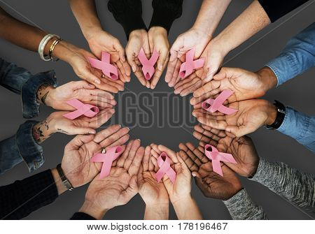 Hands holding pink ribbon for breast cancer awareness