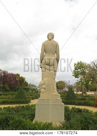 Stone statue of half-naked woman in the park