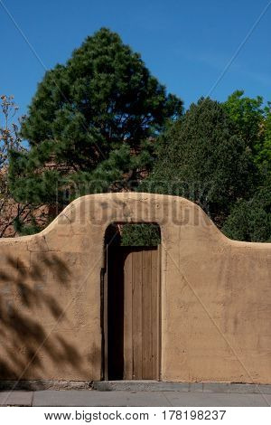 An arched door opening in an adobe wall along a street in Santa Fe, New Mexico