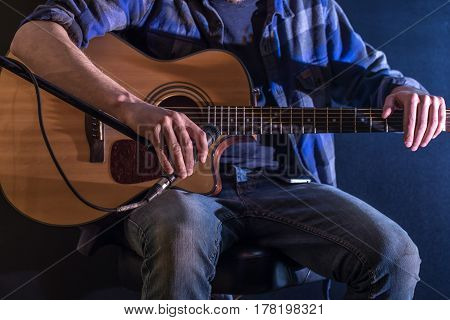 Man Playing Acoustic Guitar On A Black Background, The Music Concept, Beautiful Lighting On The Stag