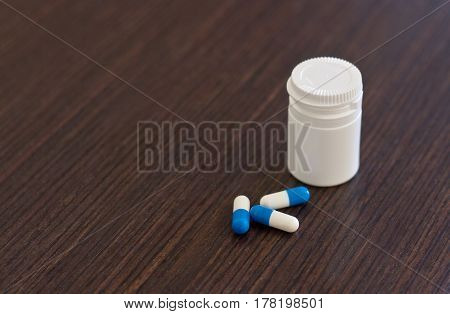 Pills spilling out of bottle on wooden background