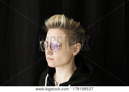 young lesbian woman with sunglasses on the black background