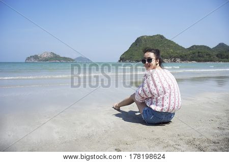 Asian teenager woman has take a relaxing on beautiful beach. Wearing sunglasses and holding a camera. Siam Smiling girl. rest time at the beach with big mountain. Filtered image. Selective focus