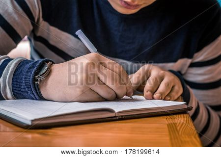 Closeup of male hands with pen writing in notebook or notepad.